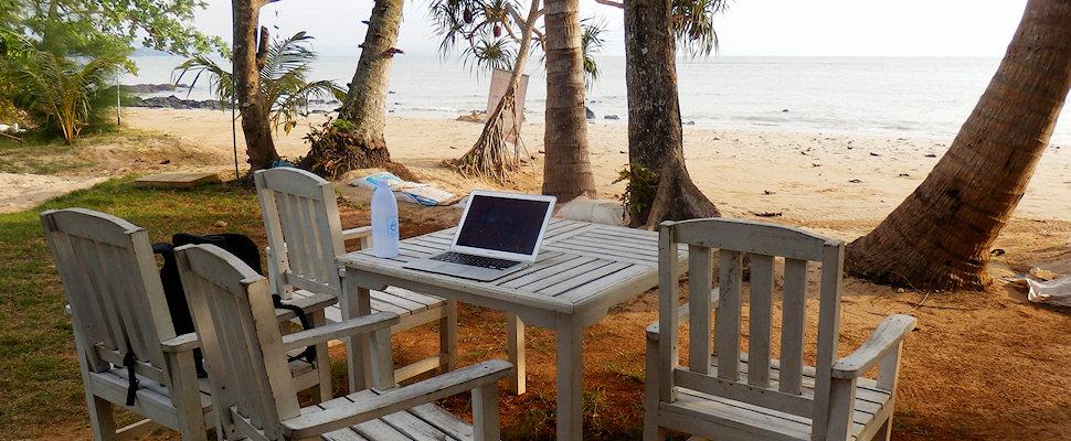Kannettava tietokone, palmuja, ranta