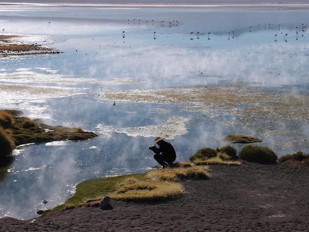 Valokuvaaja kyykistyy järven rannalle, taustalla flamingoja | Olavi Koistinen | Kulkuri.org
